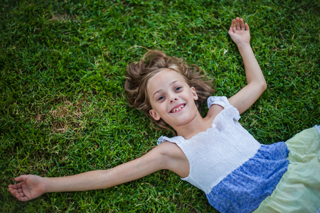 Smiling little girl lying on the grass with happy carefree expression - concept of freedom in childhood Stock Photo