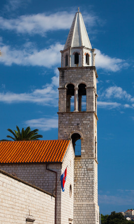 Old bell tower with Croatian flag hanging next to it (Dubrovnik, Croastia, near the port)