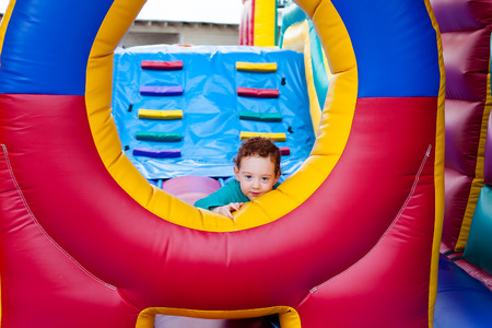 Redhead toddler gives a solemn look from trampoline