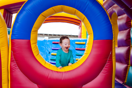 Funny toddler laughing out loud while playing on trampoline Stockfoto