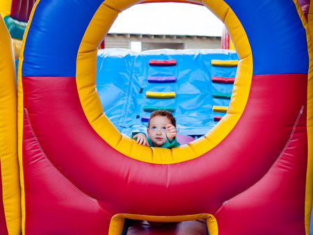 Cute toddler reaching out from trampoline castle