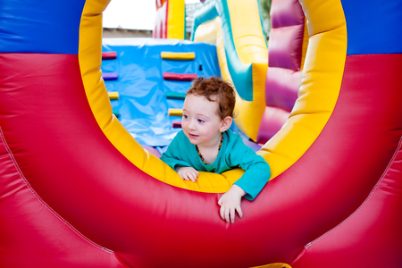 Redhead toddler during play in a trampoline castle