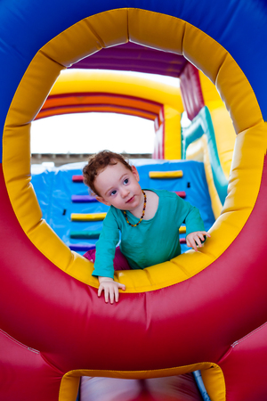 Cute toddler climbs from the window of trampoline castle Stockfoto