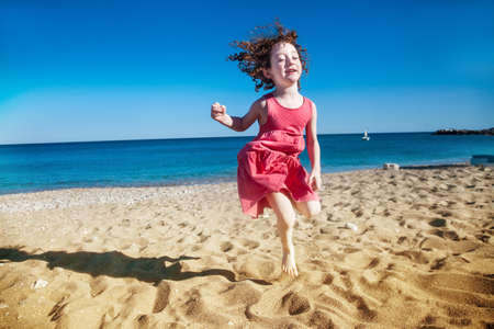 Cute little girl jumping happily with her eyes closed at seaside Stockfoto