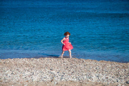 Cute redhead girl walking the sea shore holding her pink dress