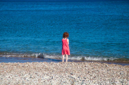 Little redhead girl in pink dress at seashore looking at the waves Stockfoto