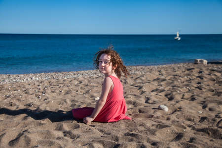 Cute little red-haired girl sits on the beach looking back to the camera