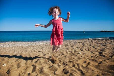 Cute little red haired girl jumping in the sand at seaside on vacation
