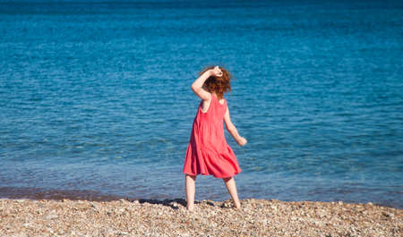 Little redhead girl in pink throwing pebbles at sea in mock pose of ancient athlete Stockfoto