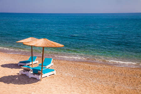 Idyllic empty tropical beach with two umbrellas and endless horizon