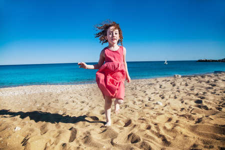 Happy cute red haired little girl in pink running on the beach