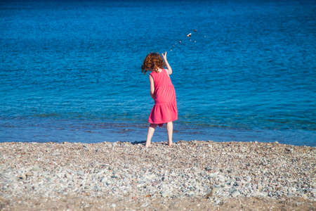 Little redhead girl in pink dress throwing stones in the sea