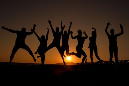 group of happy young people silhouettes jumping on the beach   on beautiful summer sunset  Archivio Fotografico