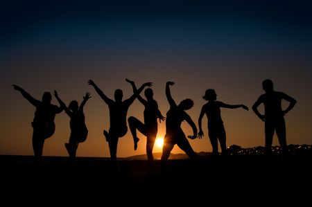 group of happy young people silhouettes dancing on the beach   on beautiful summer sunset