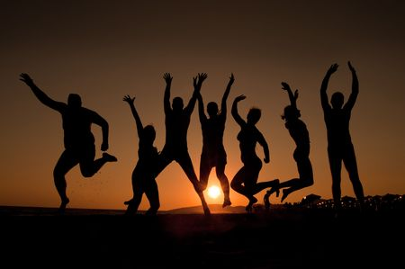group of happy young people silhouettes jumping on the beach   on beautiful summer sunset  Stock Photo