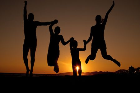 Silhouette of family jumping on the beach   on beautiful summer sunset  photo