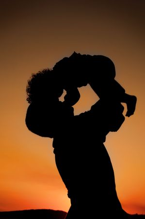 father and child: Silhouette of father and child on the beach   on beautiful summer sunset
