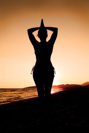 Woman doing yoga at sunset on the beach Stock Photo - 7639938