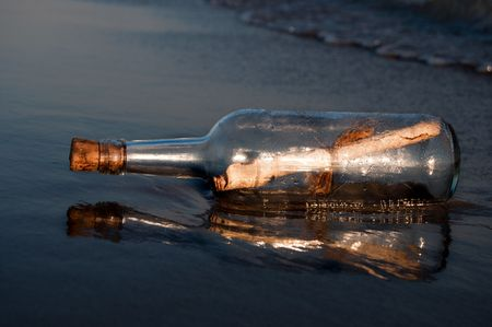 Message in a bottle stranded on the beach photo
