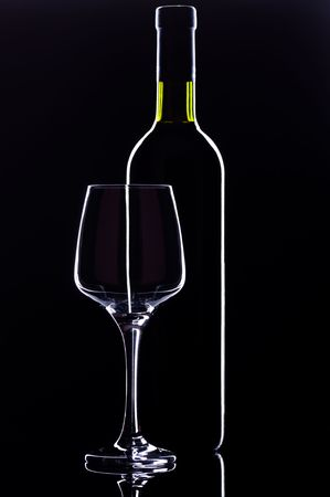 Glass of Wine and Wine Bottle on dark background