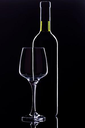 Glass of Wine and Wine Bottle on dark background