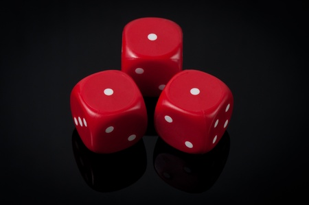 Closeup of three red dice on green background photo