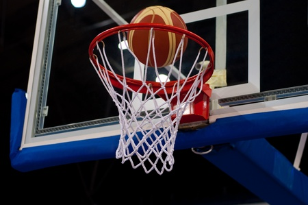 Basketball Success. Ball going through the net  Stock Photo