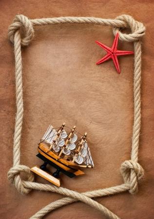 old macro: Edad de cuerda y barco sobre el antiguo fondo de papel Foto de archivo