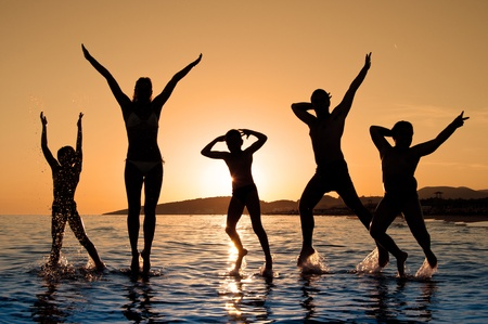 Silhouette of family jumping on the beach on beautiful summer sunset Standard-Bild