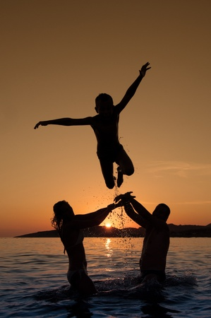 Silhouette of boy jumping on the beach on beautiful summer sunset photo