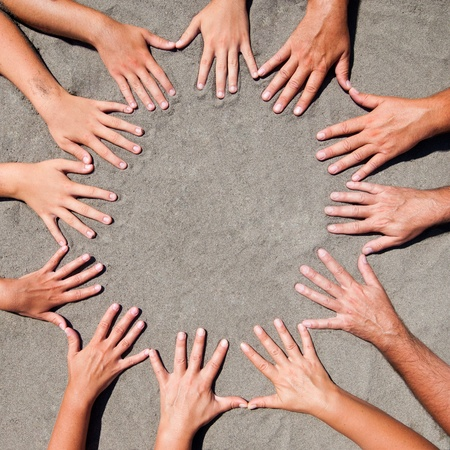 close together: Image of  hands on sand - circle form Stock Photo