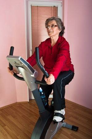 happy senior woman exercise on spinning bicycle at home