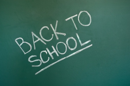 Back to school chalkboard. Green chalk blackboard written Back To School with white chalk. photo