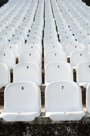 numbered: Empty white plastic seats in a stadium