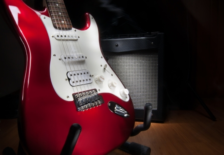 red and white electric guitar and combo amplifier on black background