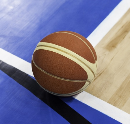 Basketball over wooden floor. Close up. photo