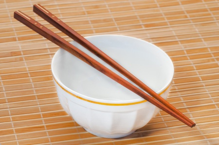 asian style bowl and chopstick on bamboo background. photo