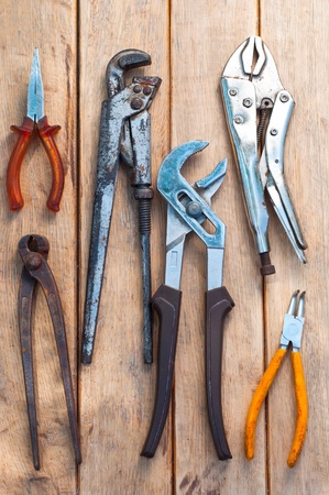 set of different pliers over wooden boards background photo