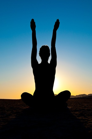Silhouette of woman in yoga lotus meditation position with arms up Standard-Bild