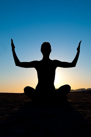 Silhouette of woman in yoga lotus meditation position with arms up Stock Photo - 12610461