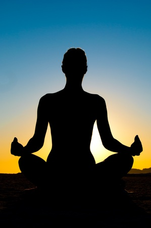 Silhouette of woman in yoga lotus meditation position Stock Photo - 12610459