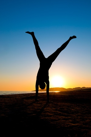 Silhouette of Young Woman Turning Cartwheel On Beach photo