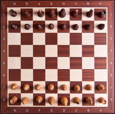 chess board: The initial setup of a chess board. The pieces and chess board are made of wood.