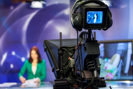 television show: Video camera viewfinder - recording show in TV studio - focus on camera