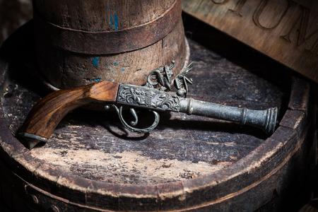 vintage gun: Model of the old vintage gun on wooden background Stock Photo