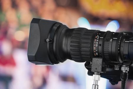 video production: Video camera lens - recording show in TV studio - focus on camera aperture Stock Photo