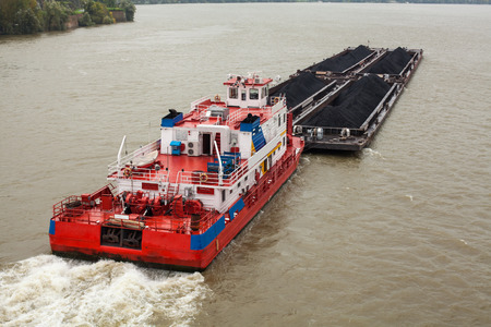 tug: Top view of Tugboat pushing a heavy barge on the river Stock Photo