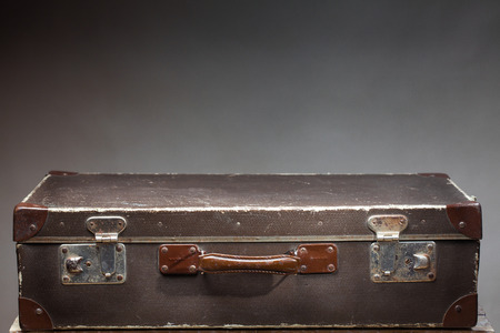 antique suitcase: Old vintage suitcase on wooden table on blank gray background