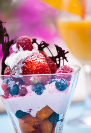 summer pudding: Fresh Fruit salad with ice cream in cup on colorful background