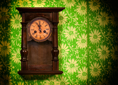 reloj de pendulo: reloj de pared de madera vieja de la vendimia que cuelga en la pared verde